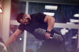 strong young man with beard wearing black sport clothes lifting heavy weight dumbbell with on hand training back in gym workout with pain and effort