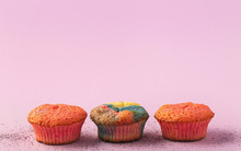 Three Colorful Muffins On A Pa...