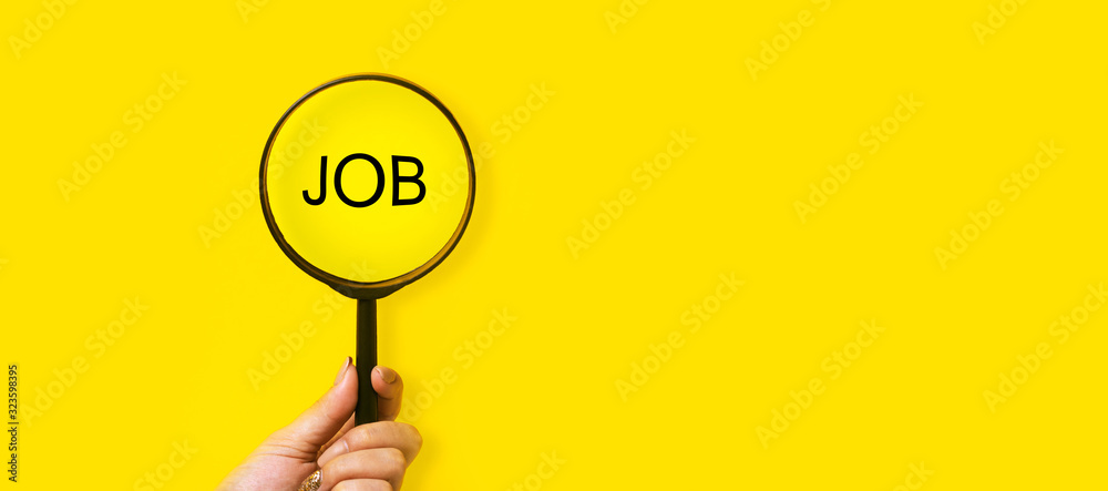 Fototapeta job search concept, inscription and magnifier in hand on a yellow background
