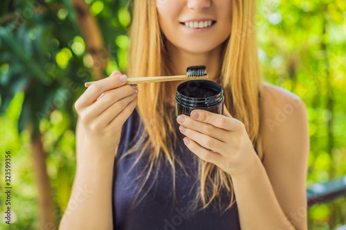 Photo Young woman brush teeth using Activated charcoal powder for brushing and whitening teeth
