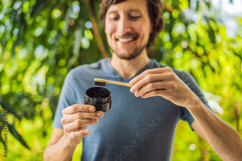 Young man brush teeth using Activated charcoal powder for brushing and whitening teeth Canvas Print