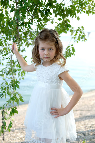 young girl in a beautiful white dress stands next to a birch tree in a park Canvas Print