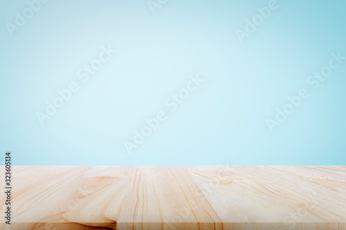 Obraz Empty wooden deck table over light blue wallpaper background for present product. - fototapety do salonu