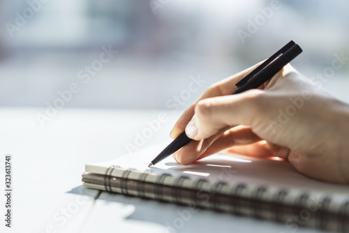 Woman writes with a pen in notebook in a sunny office, business and education concept Canvas Print