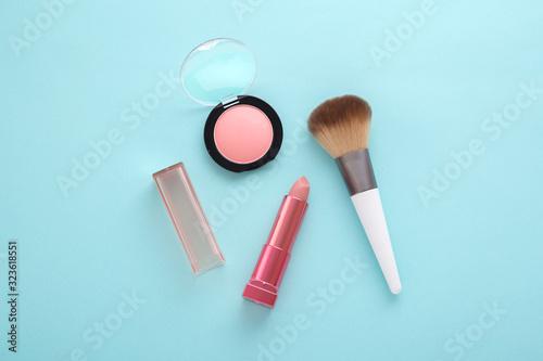 Valokuva Pink lipstick, blush and brush on blue background