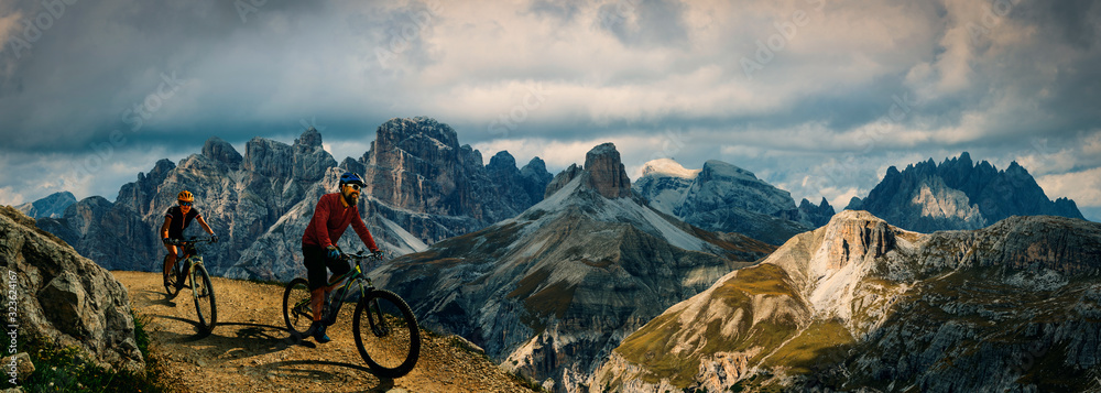 Fototapeta Cycling outdoor adventure in Dolomites. Cycling woman and man  on electric mountain bikes in Dolomites landscape. Couple cycling MTB enduro trail track. Outdoor sport activity.