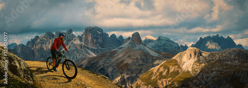 Fototapeta Cycling outdoor adventure. Man cycling on electric bike, rides mountain trail. Man riding on bike in Dolomites mountains landscape. Cycling e-mtb enduro trail track. Outdoor sport activity. obraz