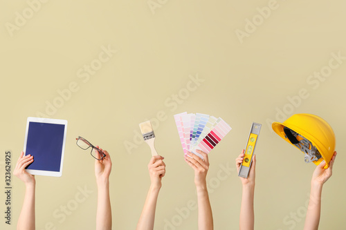 Many hands with architect's supplies and tablet computer on color background