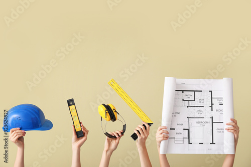 Many hands with architect's supplies on color background