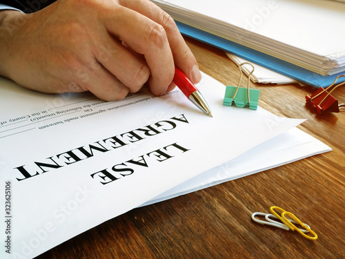 Fotomural Man is signing lease agreement by the pen.