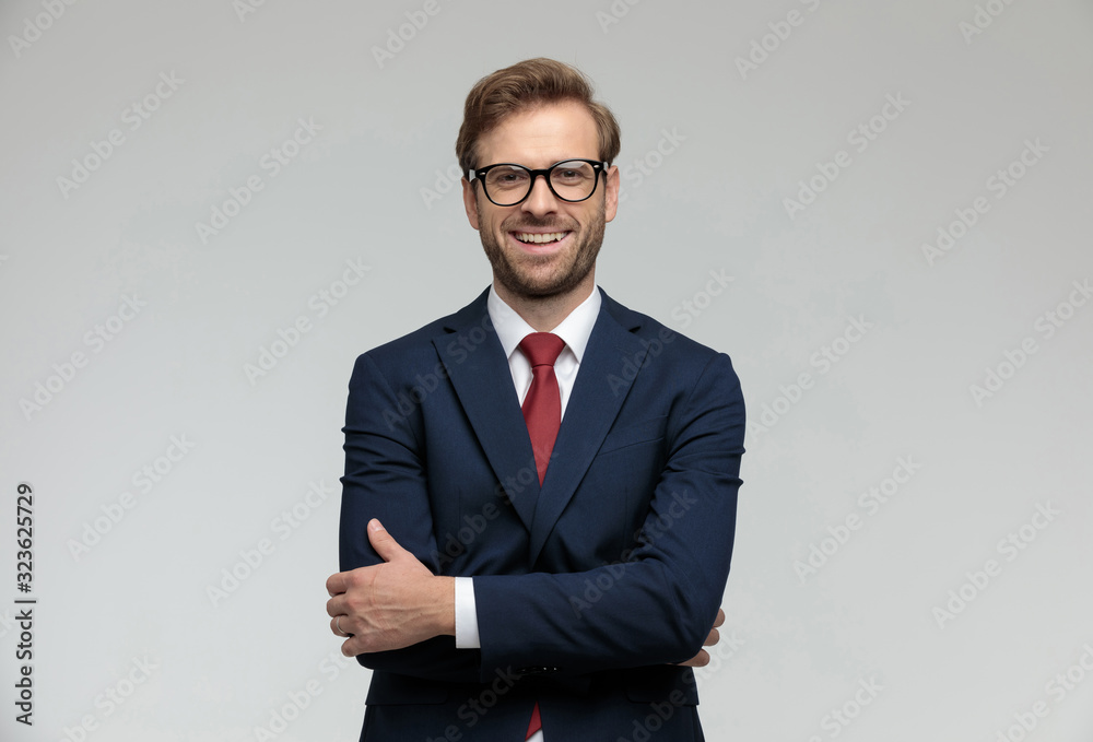 Fototapeta businessman standing with hands crossed and looking at camera happy