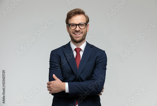 businessman standing with hands crossed and looking at camera happy
