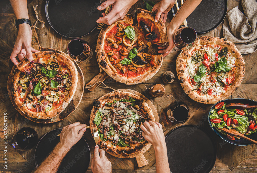 Obraz Family or friends having pizza party dinner. Flat-lay of people taking and eating various kinds of pizza and drinking red wine over rustic wooden table, top view. Fast food lunch, celebration fototapeta, plakat