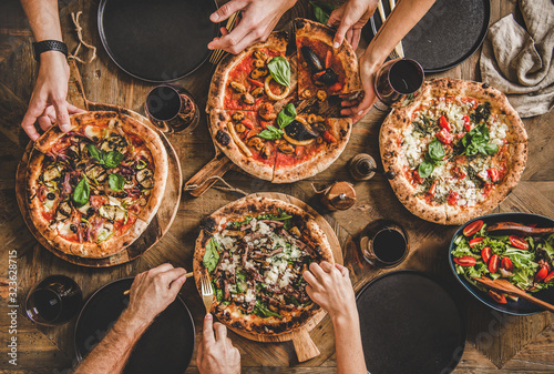 Fototapeta Family or friends having pizza party dinner. Flat-lay of people taking and eating various kinds of pizza and drinking red wine over rustic wooden table, top view. Fast food lunch, celebration obraz