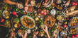 Flat-lay of family celebrating over rustic table with Turkish cuisine lamb chops, quince, green bean, vegetable salad, babaganush, rice pilav, pumpkin dessert, lemonade, top view. Middle East cuisine
