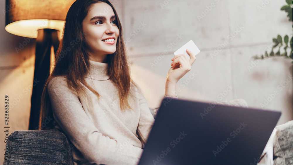 Fototapeta Girl using bank card for buying things online. Retail stores offering bonus cards for customers. Select items in web shop app, transfer money safely using sms code for payment.