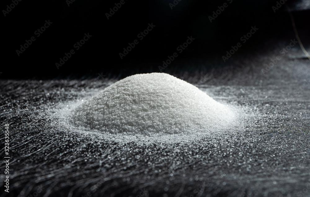 Heap of sugar on a dark background. <span>plik: #323635548 | autor: Chinnabuth</span>