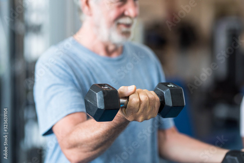 close up of mature man holding two dumbbells doing exercise at the gym to be hea Canvas Print