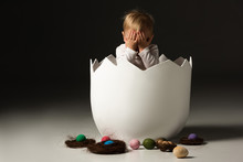 Child Covering Face Inside Eggshell Next To Easter Eggs And Nests On Black Background