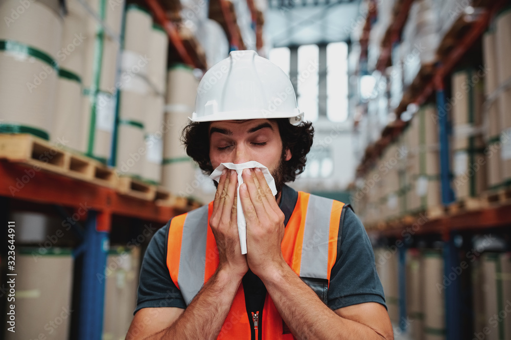 Fototapeta Young warehouse manager coughing and sneezing while feeling sick and covering mouth with handkerchief standing in factory
