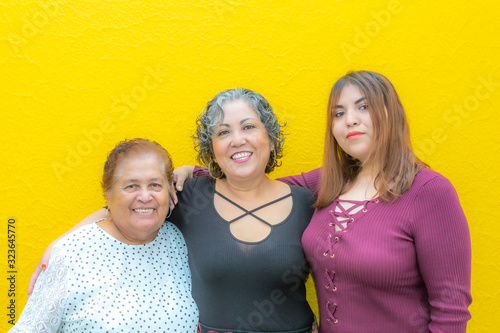 Three generations of latin Mexican women smiling, grandmother, daughter and gran Canvas Print