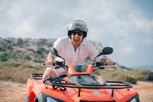 A Man Sits On A Quad In A Helmet And Glasses In The Mountains