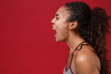 Side View Of Crazy Young African American Sports Fitness Woman In Sportswear Working Out Isolated On Red Wall Background In Studio. Sport Exercises Healthy Lifestyle Concept. Looking Aside, Screaming.