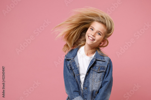 Fotografie, Tablou Smiling little blonde kid girl 12-13 years old in denim jacket isolated on pastel pink background children portrait