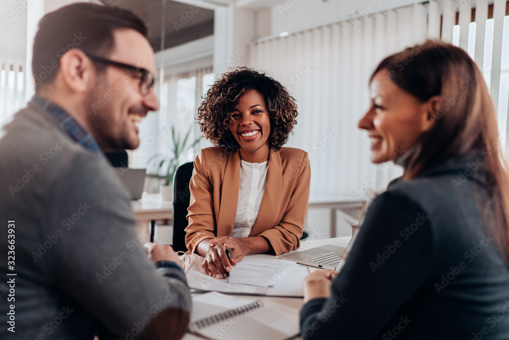 Fototapeta Couple consulting with a female financial manager at the bank
