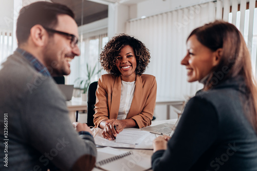 Couple consulting with a female financial manager at the bank