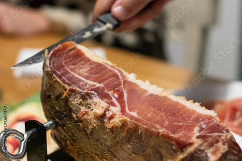 Photo Mano de hombre corta jamón curado con cuchillo con una rodaja muy delgada en cas