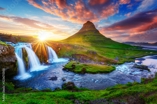 Gorgeous landscape with rising sun on Kirkjufellsfoss waterfall and Kirkjufell mountain, Iceland, Europe.