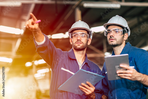 Fotografia Two engineer worker working together with safety uniform and white helmet to work in industry factory handle tablet