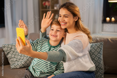 family, technology and people concept - happy smiling mother and little son with smartphone having video call and waving hands at home