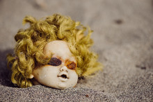 Creepy Head Of The Doll In Sand Washed By Ocean On The Beach