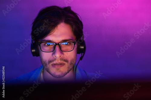 фотография Gamer At Desktop PC Playing Game At Home At Night