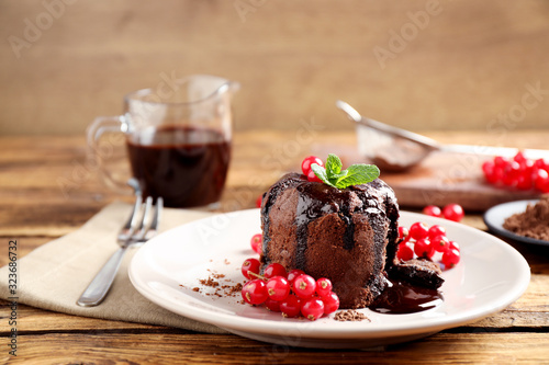 Delicious warm chocolate lava cake with mint and berries on wooden table