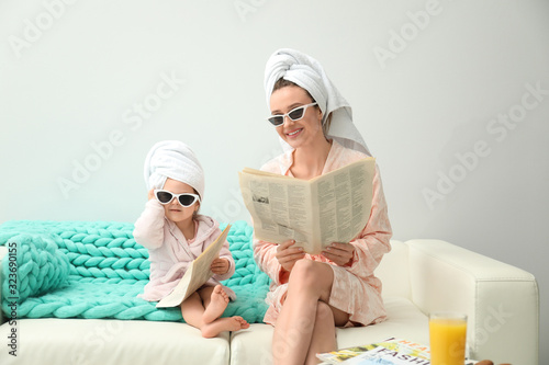 Mother and little daughter in bathrobes with newspapers sitting on sofa