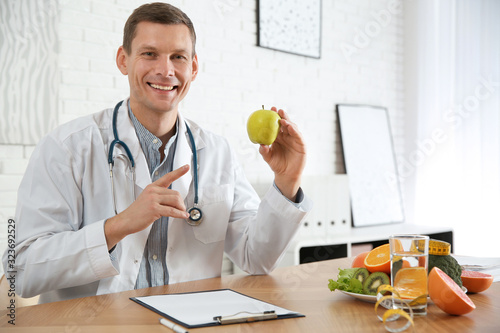 Nutritionist with apple at desk in office