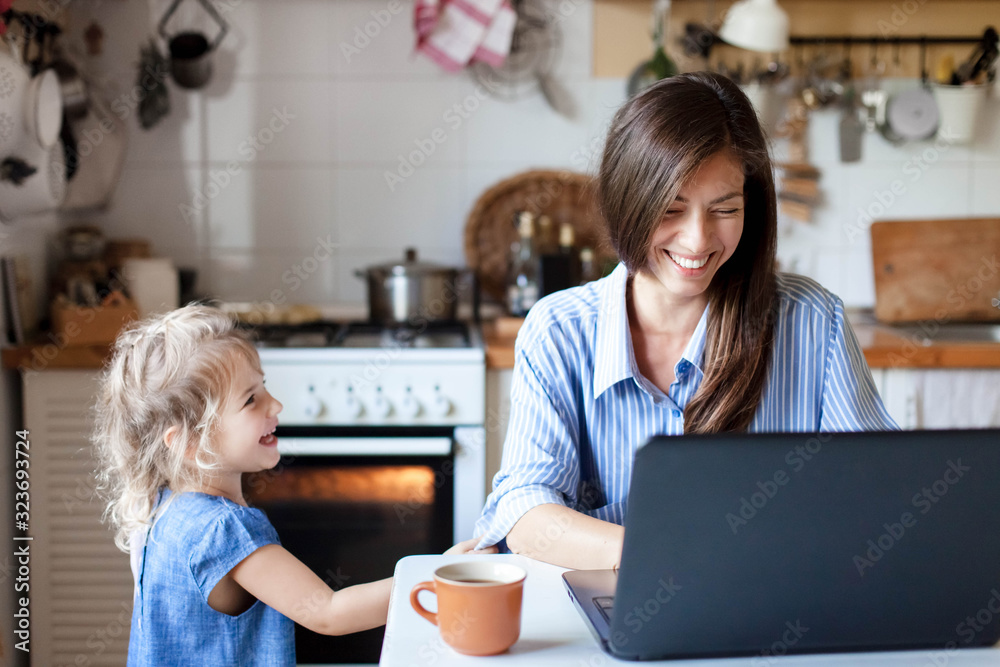 Fototapeta Working mom works from home office. Happy mother and daughter smiling. Successful woman and cute child using laptop. Freelancer workplace in cozy kitchen. Female business. Lifestyle authentic moment.