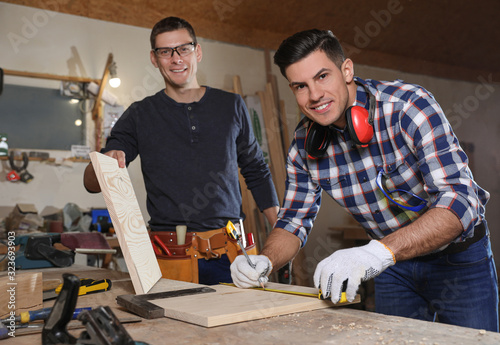 Professional carpenters working with wooden boards in workshop