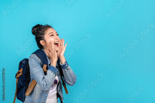 Photo Happy asian woman travel backpacker shouting open mouth to copyspace on blue background