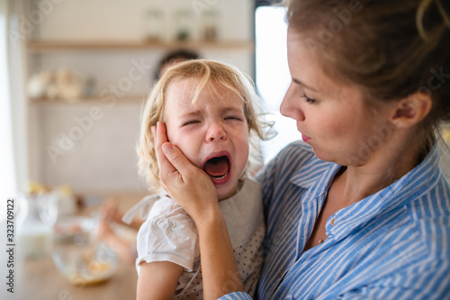 Photo A mother holding a crying toddler daughter indoors in kitchen.