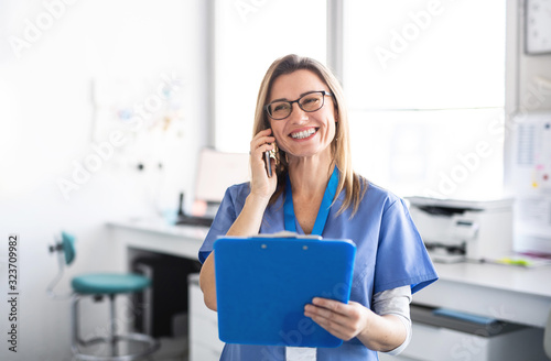 A portrait of dental assistant in modern dental surgery, using smartphone Canvas Print
