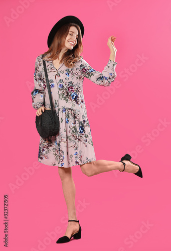 Young woman wearing floral print dress with stylish handbag and hat on pink background
