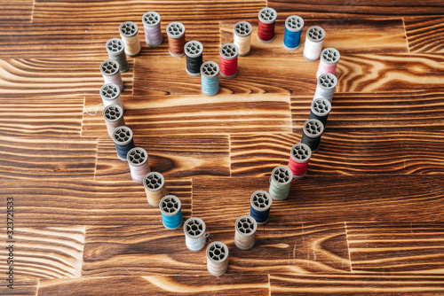 Many side by side aline thread spools in a heart shape on a wooden background Wallpaper Mural