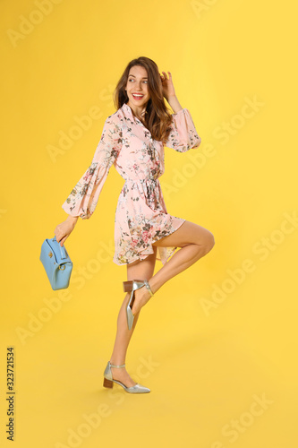 Young woman wearing floral print dress with stylish handbag on yellow background