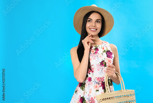 Young woman wearing floral print dress with straw bag on light blue background. Space for text