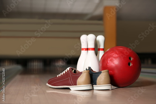 Shoes, pins and ball on bowling lane in club
