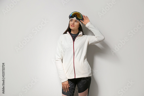 Woman wearing fleece jacket and goggles on light grey background. Winter sport clothes
